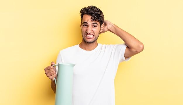 Przystojny latynos czuje się zestresowany, niespokojny lub przestraszony, z rękami na głowie. koncepcja termosu do kawy