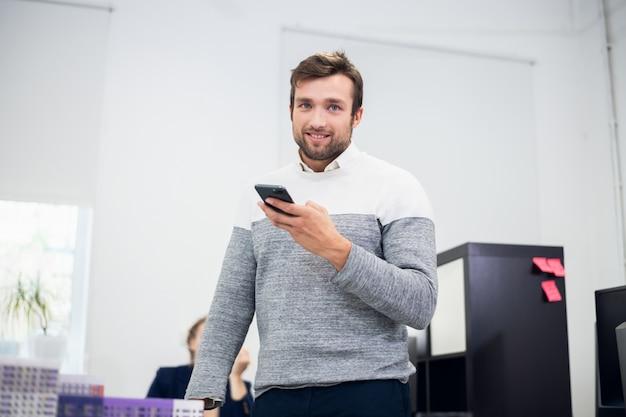 Przystojny latynoski biznesmen patrzeje kamerę z smartphone w jego ręce