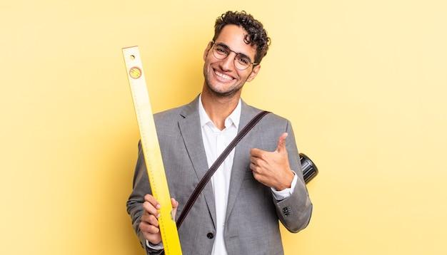 Przystojny latynoski mężczyzna czuje się dumny, uśmiechając się pozytywnie z kciukami do góry. koncepcja architekta