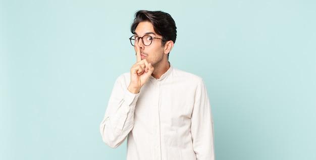 """Przystojny latynoski mężczyzna proszący o ciszę i spokój, gestykulujący palcem przed ustami, mówiący """"cii"""" lub dochowujący tajemnicy"""