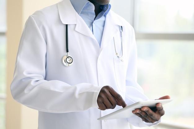 Przystojny lekarz afroamerykanin trzymający cyfrowy tablet w szpitalu