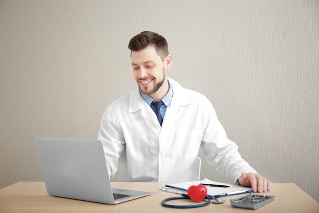 Przystojny lekarz pracujący na laptopie w miejscu pracy
