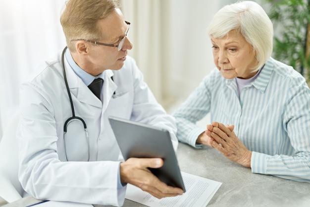 Przystojny lekarz siedzi przy stole i wskazuje na elektroniczny komputer stacjonarny podczas rozmowy ze starszą panią w swoim gabinecie