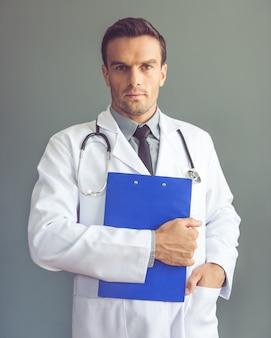 Przystojny lekarz w białym płaszczu trzyma folder