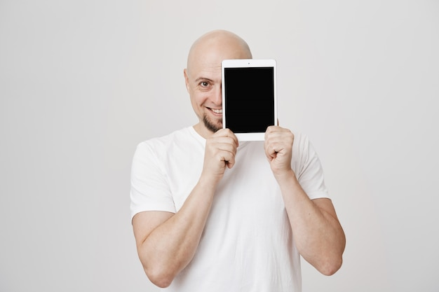 Przystojny łysy mężczyzna pokazuje cyfrowy ekran tabletu, uśmiechając się zadowolony