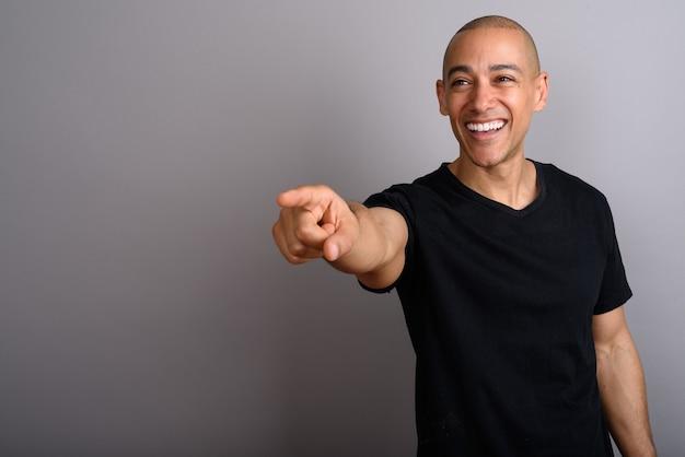 Przystojny łysy mężczyzna ubrany w czarną koszulę na szaro
