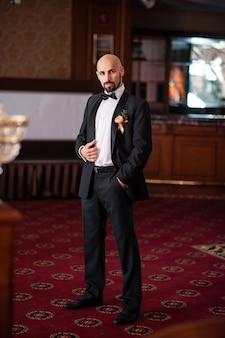 Przystojny łysy mężczyzna w czarnym garniturze