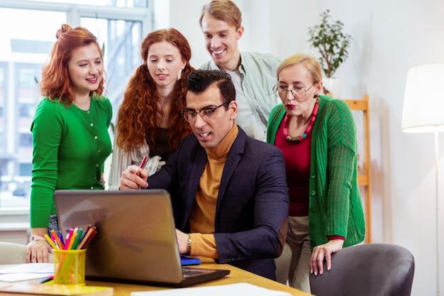 Przystojny mądry mężczyzna siedzący przy laptopie podczas rozmowy o biznesie