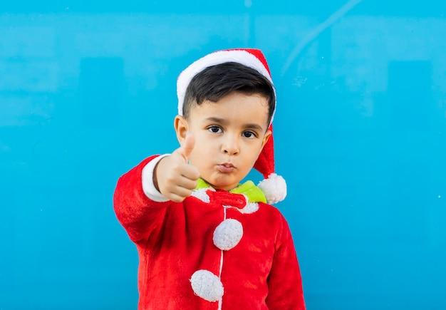 Przystojny mały chłopiec czapka świętego mikołaja, ok gest, niebieskie tło