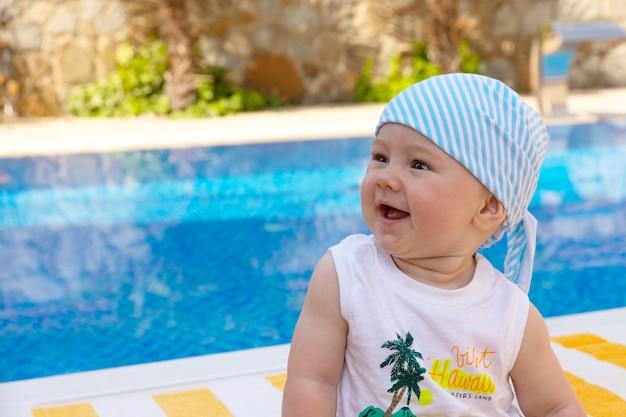 Przystojny, mały chłopiec siedzi na leżaku przy basenie. selektywne skupienie.