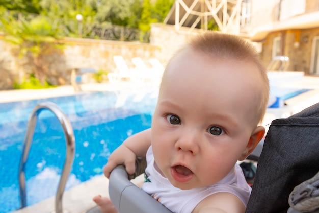 Przystojny mały chłopiec siedzi w wózku przy basenie. selektywne skupienie