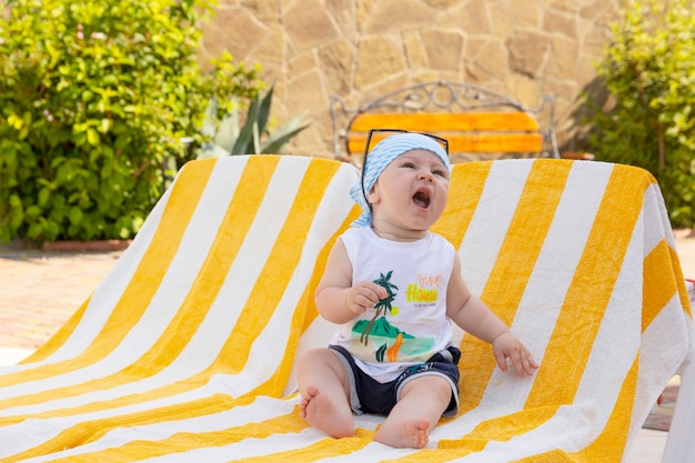 Przystojny mały chłopiec w okularach przeciwsłonecznych i chustce siedzi na leżaku przy basenie. selektywne skupienie.