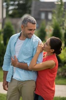 Przystojny mąż. ciemnowłosa atrakcyjna kobieta mówiąca i patrząca na swojego przystojnego męża