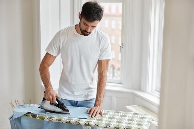 Przystojny mąż prasuje ubrania na desce do prasowania