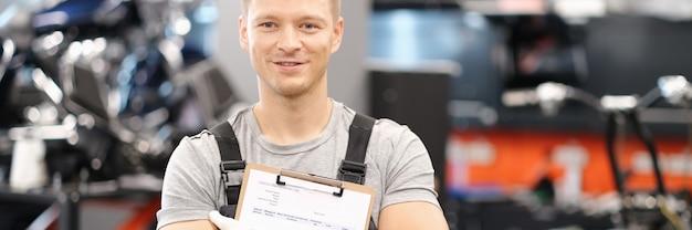 Przystojny mechanik samochodowy pozuje w serwisie samochodowym i trzyma dokumenty w rękach