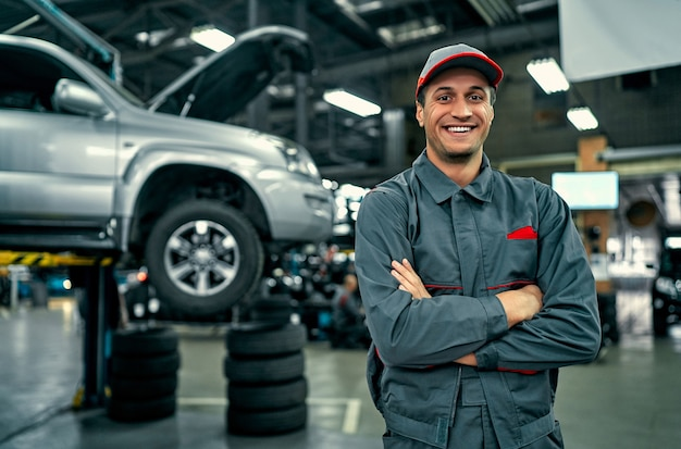 Przystojny mechanik serwis samochodowy w mundurze stoi na tle samochodu z otwartą maską, uśmiecha się i patrząc na kamery. naprawa i konserwacja samochodów.