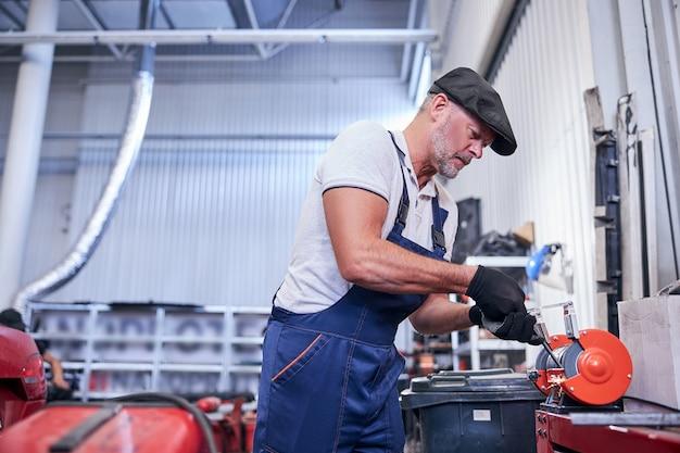 Przystojny mechanik szlifujący metalową część samochodu w garażu