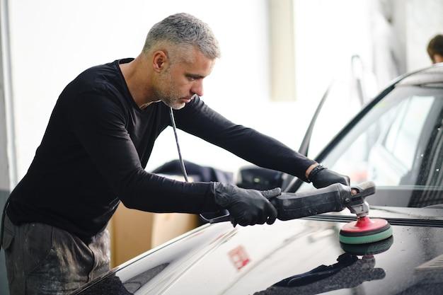 Przystojny mechanik w średnim wieku pracuje nad samochodem