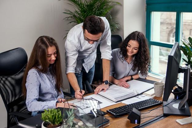 Przystojny menedżer firmy w okularach wyjaśnia zadania robocze dla swoich pracowników. kreatywni ludzie lub koncepcja biznesowa reklamy. praca zespołowa. młodzi piękni ludzie pracuje w biurze wpólnie.
