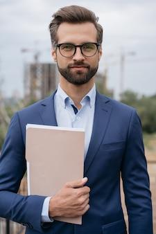 Przystojny menedżer ubrany w garnitur i okulary, trzymający dokumenty biznesowe, patrząc na kamerę
