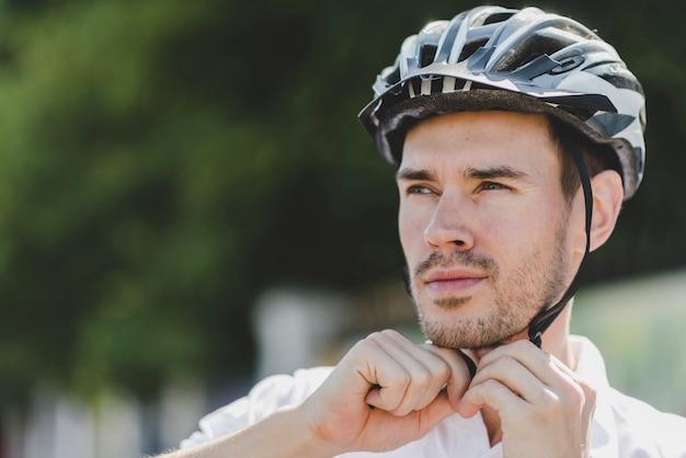Przystojny męski cyklista jest ubranym hełm patrzeje daleko od