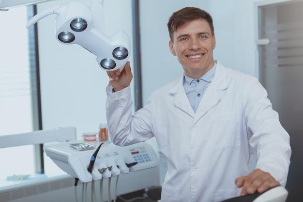 Przystojny męski dentysta pracuje przy jego kliniką