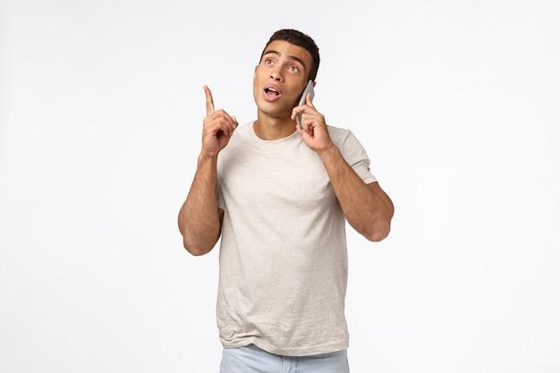 Przystojny męski młody człowiek w koszulce, trzymając smartfon w pobliżu ucha, podnosząc jeden palec