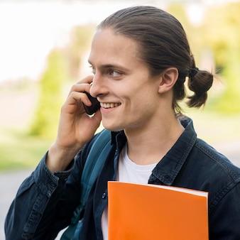 Przystojny męski uczeń opowiada na telefonie