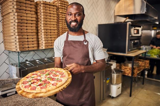 Przystojny mężczyzna afroamerykański, patrzący w kamerę i uśmiechający się, trzymając drewnianą deskę z pizzą