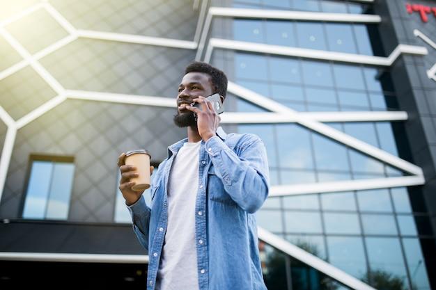 Przystojny mężczyzna afryki rozmawia przez telefon w parku.