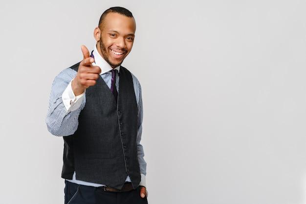 Przystojny mężczyzna amerykańsko-afrykański wskazując, stojąc przed szarej ścianie