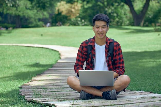 Przystojny mężczyzna azjatyckich siedzi w ogrodzie za pomocą laptopa