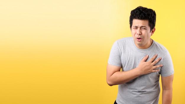 Przystojny mężczyzna azji z bólem serca, na żółtej ścianie.