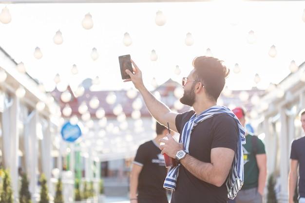 Przystojny mężczyzna bierze selfie odkryty - kaukaski ludzie - natura, ludzie, styl życia i koncepcja technologii.