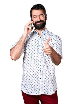 Przystojny mężczyzna brunetka z brodą rozmawia z telefonem komórkowym
