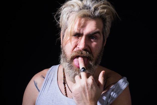Przystojny mężczyzna brutalny mężczyzna pokazuje środkowy palec brutalny brodaty mężczyzna zły facet brutalność brodaty mężczyzna lizać