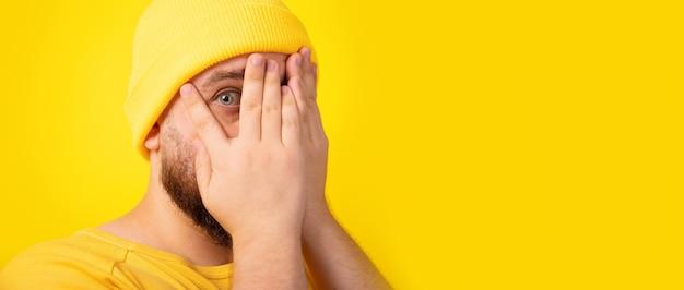 Przystojny mężczyzna chowa twarz rękami, patrząc przez dłonie, czuje się nieśmiały na żółtym tle, obraz panoramiczny