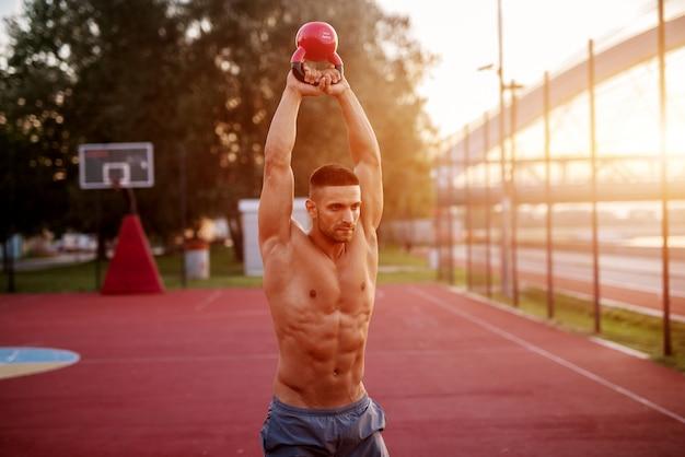 Przystojny mężczyzna ćwiczenia robocze wczesnym rankiem z wschodem słońca. trening fitness na świeżym powietrzu.