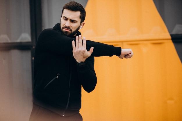Przystojny mężczyzna ćwiczy w parku w sportach jest ubranym