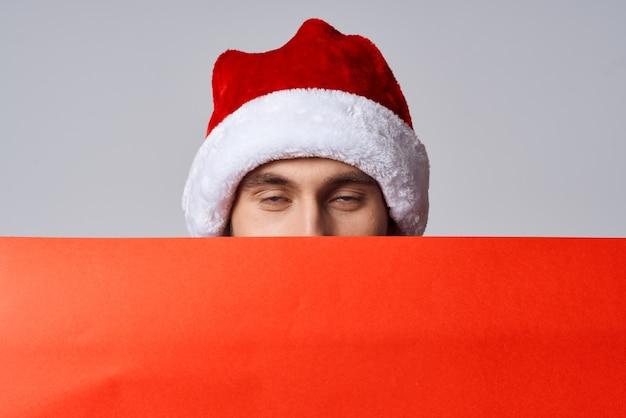 Przystojny mężczyzna czerwony papier billboard reklama boże narodzenie światło tło