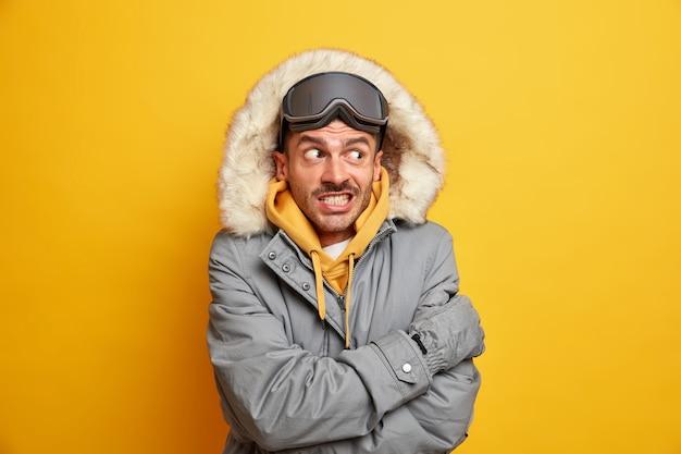 Przystojny mężczyzna czuje bardzo zimno na dworze drży w mroźny dzień przytula się do ciepłego zaciska zęby ubrany w zimowy płaszcz z kapturem.