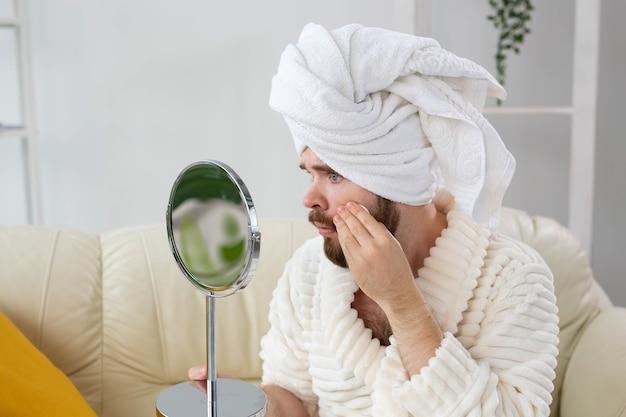 Przystojny mężczyzna czyści skórę twarzy za pomocą wacików do pielęgnacji ciała i skóry dla męskiej koncepcji