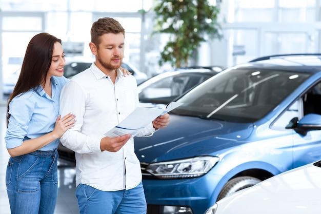 Przystojny mężczyzna czyta broszurę reklamową w salonie samochodowym, a jego piękna żona obejmuje