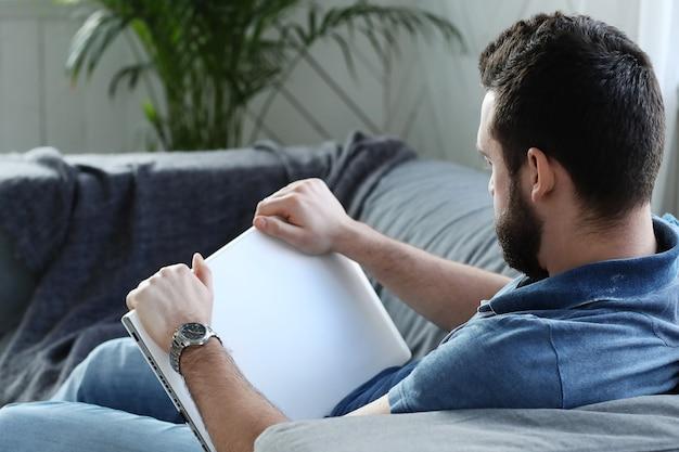 Przystojny mężczyzna czyta książkę na kanapie
