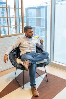 Przystojny mężczyzna degustujący kieliszek białego wina siedzący w swoim salonie