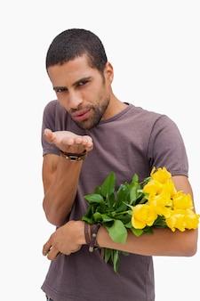 Przystojny mężczyzna dmucha buziaka i trzyma żółte róże na białym tle