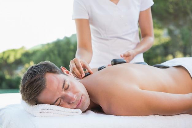 Przystojny mężczyzna dostaje gorącego kamiennego masażu poolside