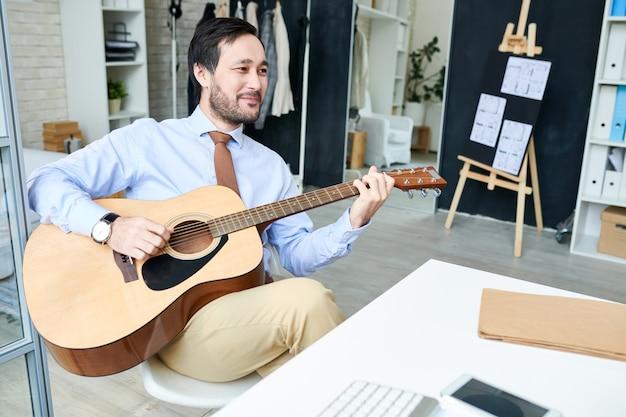 Przystojny mężczyzna enjoyin gitara w biurze