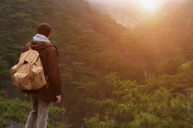 Przystojny mężczyzna faceta turysta stoi samotnie halnym lasu krajobrazem podczas jego spadku wakacje z jego plecaka widok z tyłu
