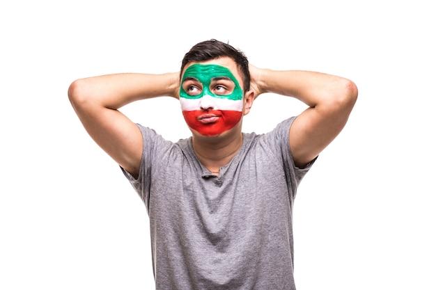 Przystojny mężczyzna, fan kibiców reprezentacji iranu, pomalowany flagą, dostaje nieszczęśliwe smutne sfrustrowane emocje do aparatu. emocje fanów.